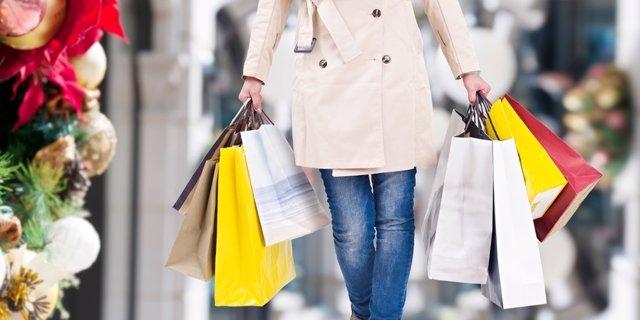 Mujer camina con regalos, compras