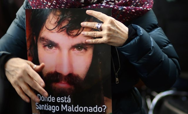 A woman holds a portrait of Santiago Maldonado, a protester who has been missing