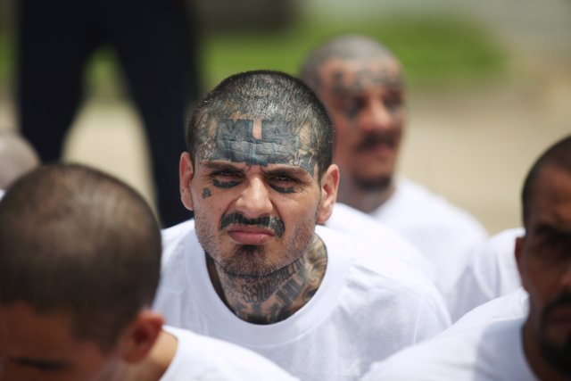 Mara Salvatrucha (MS-13) gang members wait to be escorted upon their arrival at