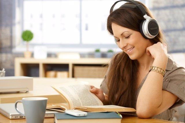 Chica estudiando con cascos y música