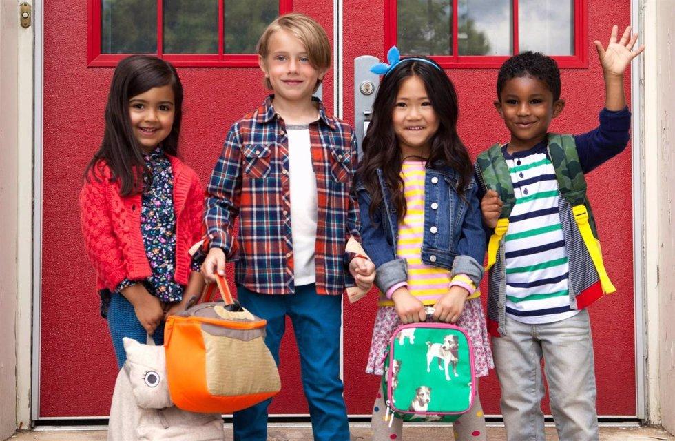 Portrait of elementary schoolgirls and boys waving from elementary school doorwa