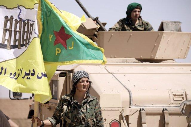 Una miliciana de las FDS junto a un carro de combate
