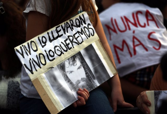 A girl holds a portrait of Santiago Maldonado, a protester who has been missing