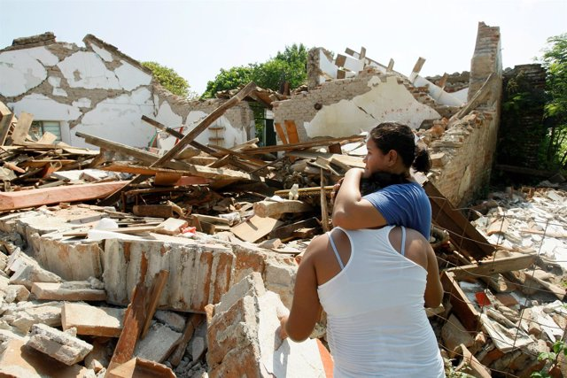 Women hug while standing next to a destroyed house after an earthquake struck th