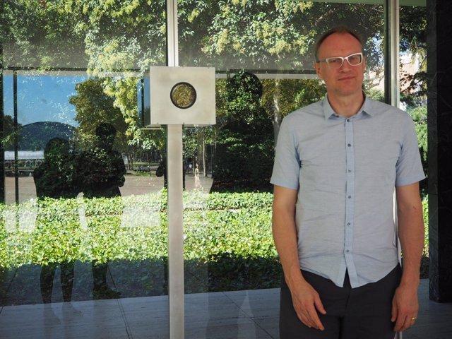 El fotógrafo Michael Wesley junto la cámara que ha instalado en el pabellón