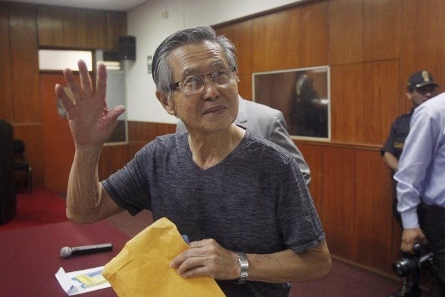 Peru's former President Alberto Fujimori waves to the media as he arrives in cou