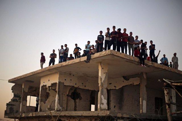 Personas sobre un edificio en el paso de Rafá, en el sur de la Franja de Gaza