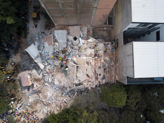 Search and rescue operations are carried out at the site of a collapsed building