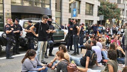 Unos 50 concentrados se mantienen en Exteriores en torno a dos coches de Guardia Civil