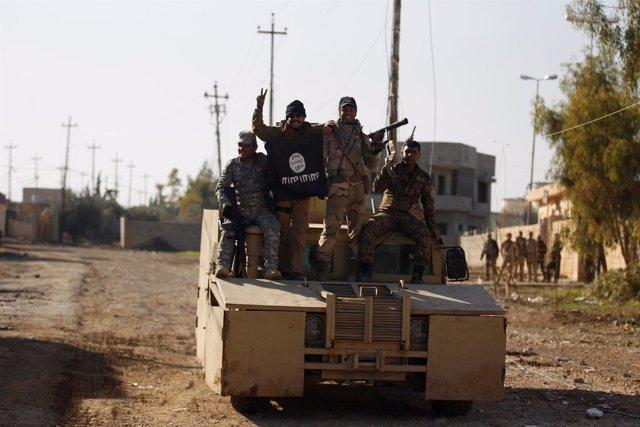 Militares iraquíes posan con la bandera de Estado Islámico en Mosul