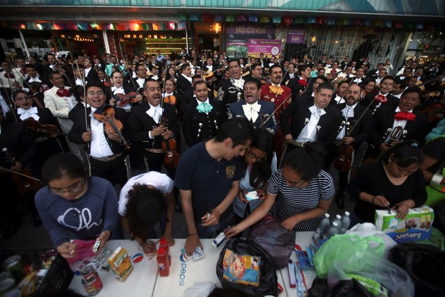 Mariachi musicians perform at Garibaldi square to trade their music for supplies