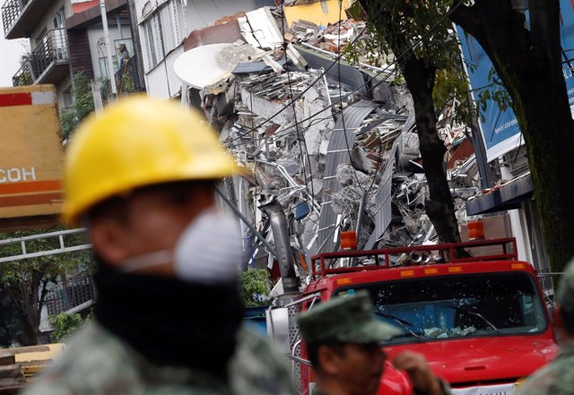 A soldier looks on next to a collapsed building after an earthquake in Mexico Ci