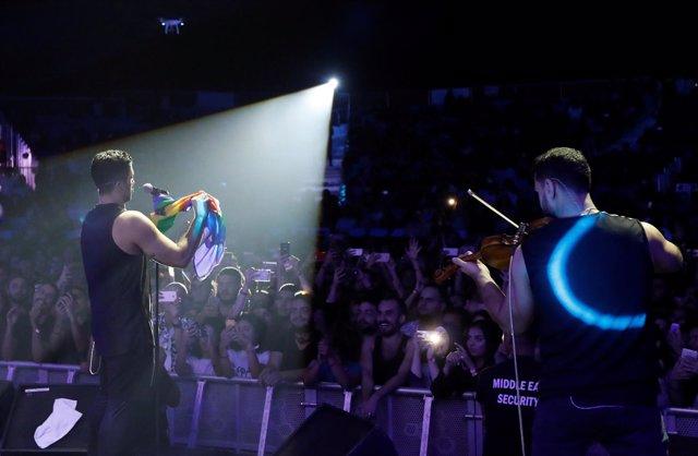 El cantante de Mashrou' Leila con una bandera arcoiris en un concierto en Líbano