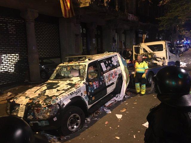 Una grúa retira un coche destrozado de la Guardia Civil en Barcelona