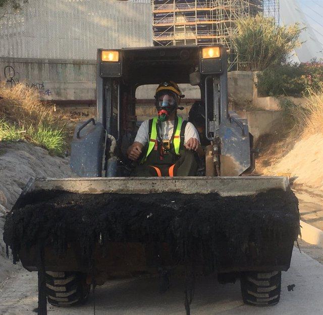 Técnico cargando toallitas del Colector Norte con una excavadora