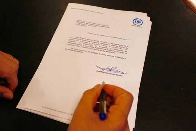 El presidente del PP-A, Juanma Moreno, firma su renuncia como senador