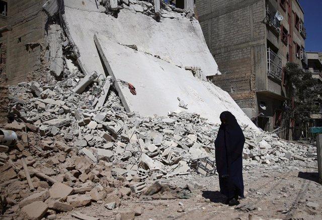 Una mujer al pie de un edificio derrumbado por un bombardeo en Damasco