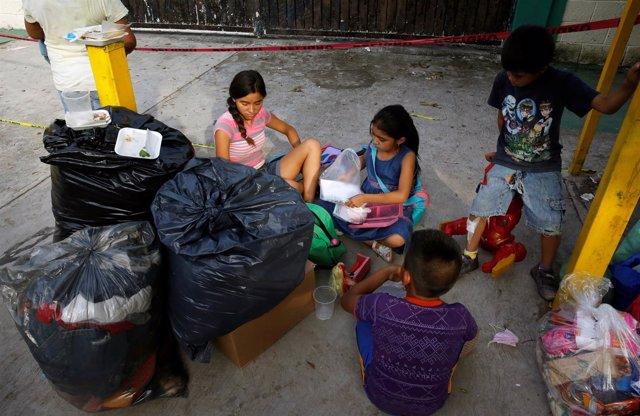 Niños sentados en el suelo tras los terremotos de México