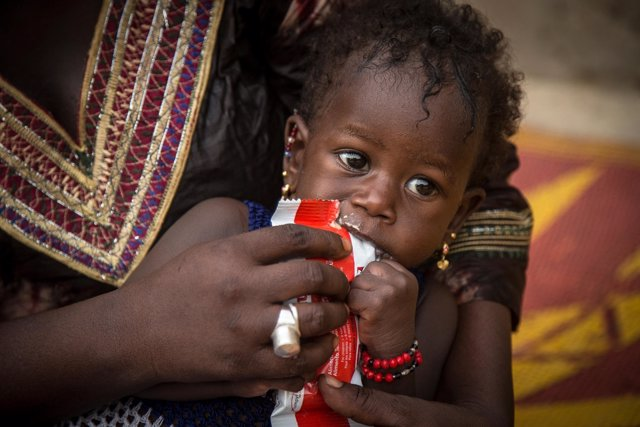 Una niña maliense tomando una barrita energética