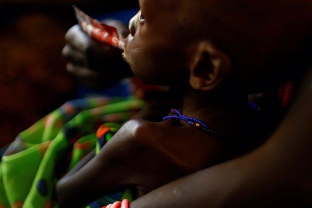 Una madre alimenta a su hijo con una barrita nutritiva en Sudán del Sur