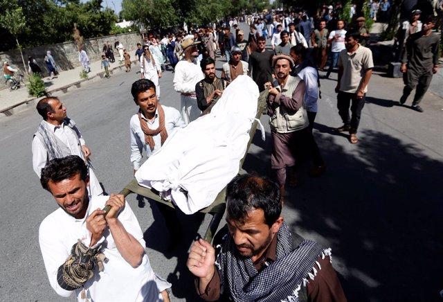 Manifestantes portando el cadáver de uno de los muertos por disparos de policías