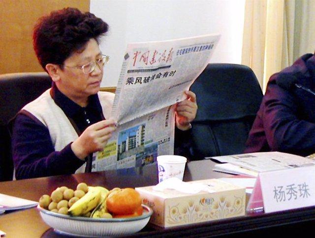 Yang Xiuzhu reads a newspaper during a meeting in Wenzhou, Zhejiang province, De