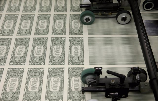 Sheets of United States one dollar bills are seen during the production process