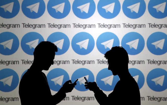 Two men pose with smartphones in front of a screen showing the Telegram logos in