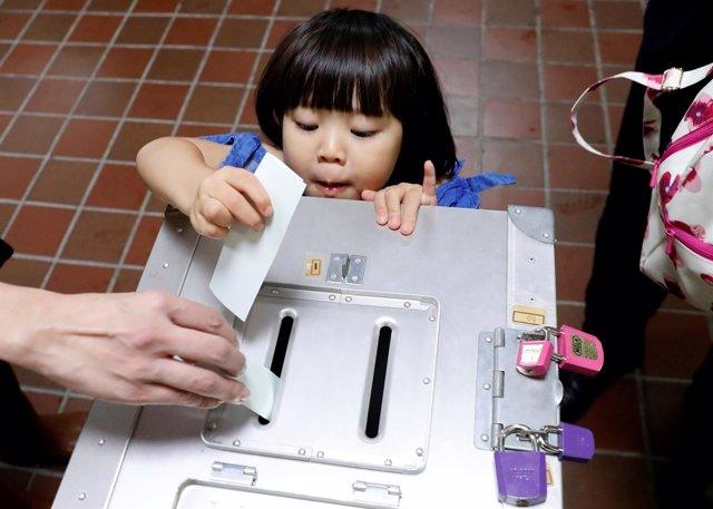 Una niña deposita el voto de su padre en las elecciones de Japón