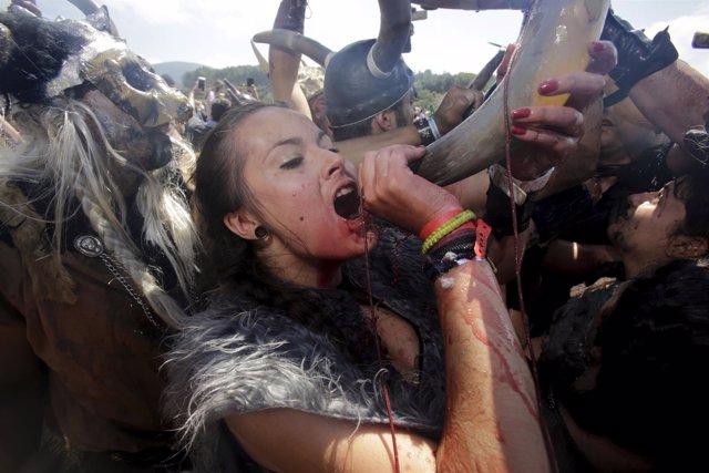 Una mujer vestida de vikinga bebe vino