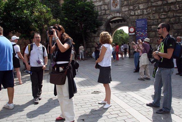 Turistas recorriendo Sevilla.