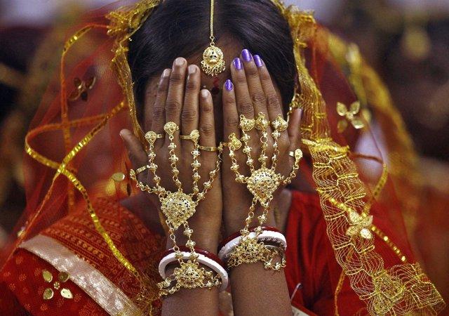 Una novia india cubre su cara