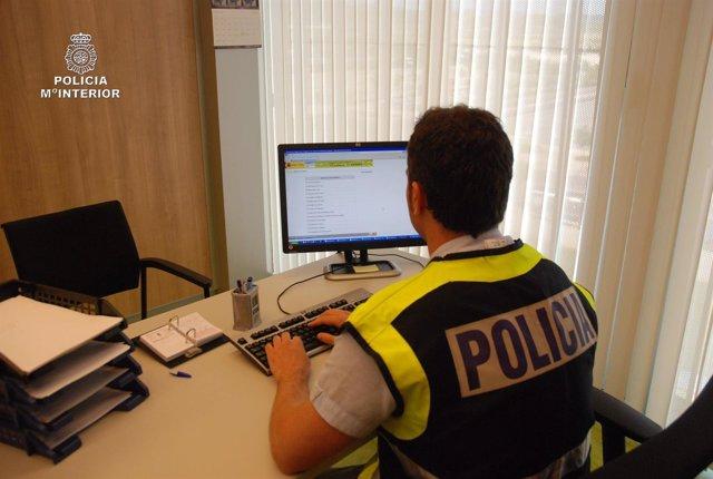 Policia con ordenador, en busca de pedófiles en la red.