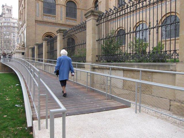 Una persona mayor camina por la rampa accesible del Paraninfo