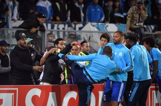 Patrice Evra dando una patada a un aficionado de su equipo