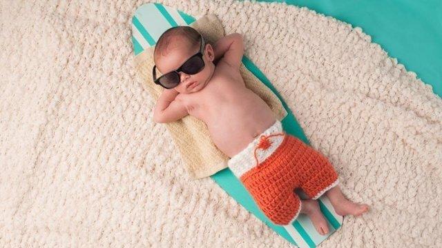 Bebé con postura cool en una tabla de surf