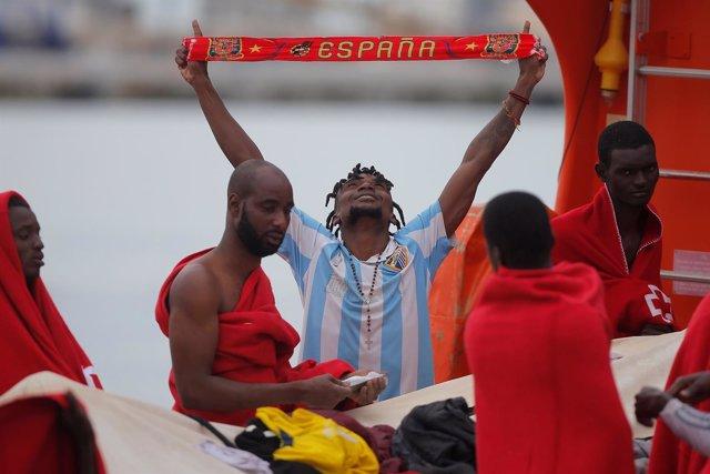 Un inmigrante rescatado celebra su llegada al puerto de Málaga