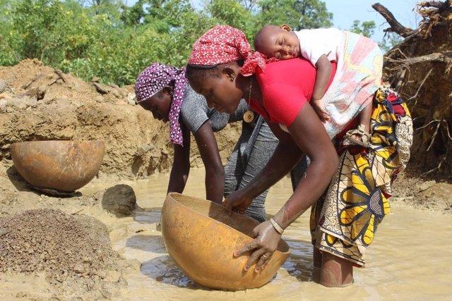 Niña trabaja con su hija a la espalda en un yacimiento de oro en Malí