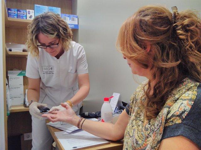Una farmacéutica realiza una prueba de glucemia a una usuaria
