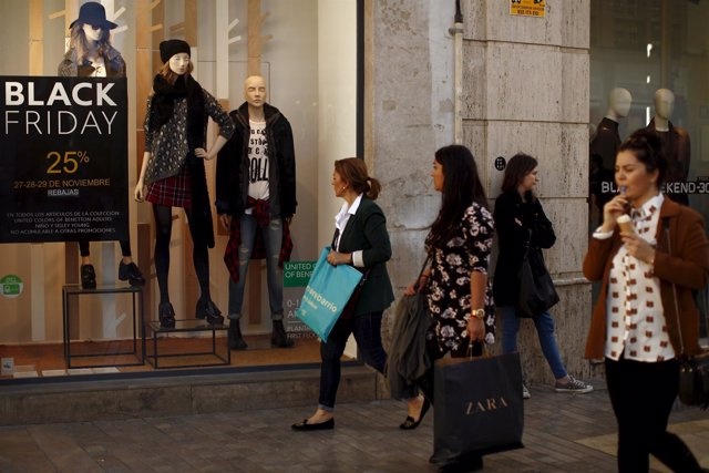 Women carry shopping bags during the Black Friday sales in downtown Malaga, sout