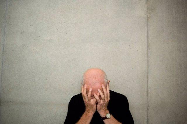 Un hombre mayor tapa su rostro, deprimido por el Alzheimer.