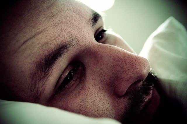 Hombre triste en la cama