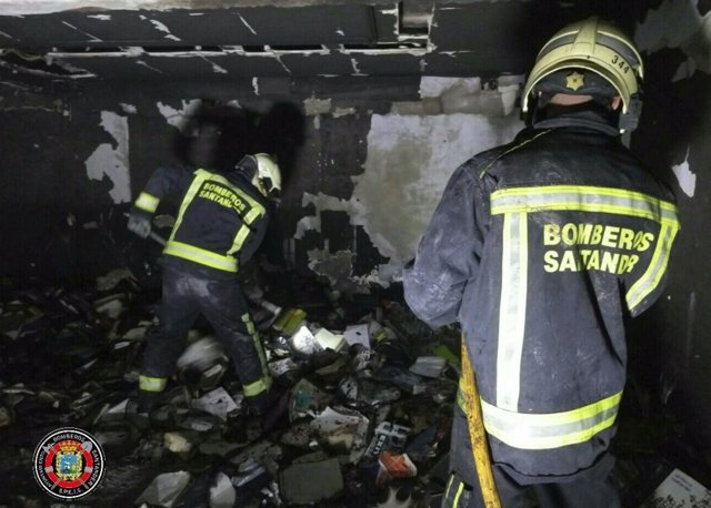 Bomberos trabajan en la extinción del incendio. En la imagen se aprecian libros