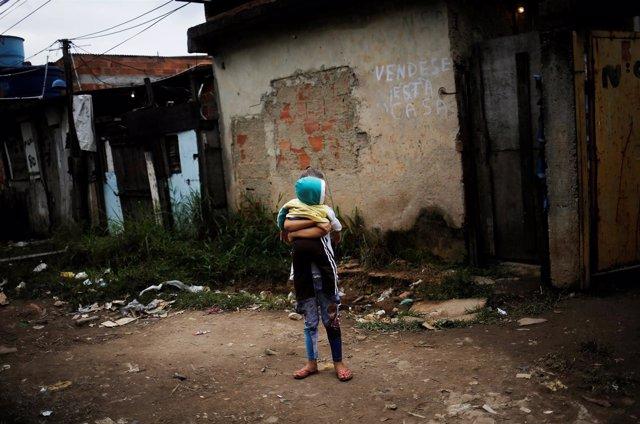Niña brasileña con un bebé en brazos en medio de la favela en la que vive