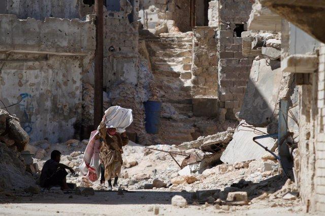 Mujer camina entre edificios destruidos en Alepo (Siria)