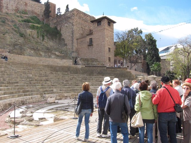 Turistas En El Teatro Romano De Málaga.