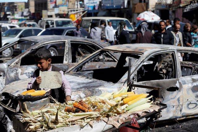 Un niño junto a coches destruidos en los combates en Saná