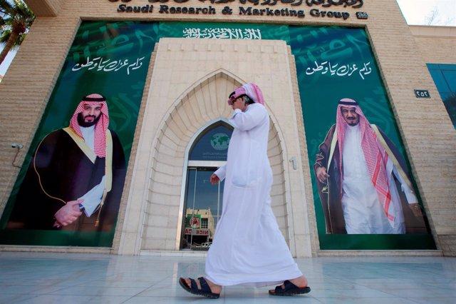 Un hombre frente a carteles del rey Salman y el príncipe heredero