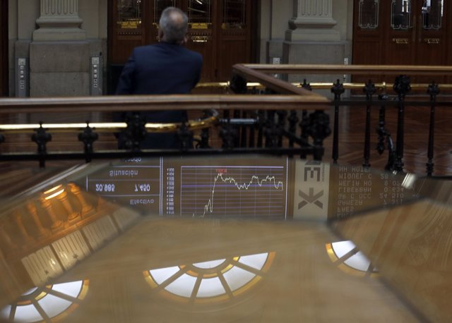 A trader talks on the phone as he looks at an index screen at Madrid's Bourse Oc
