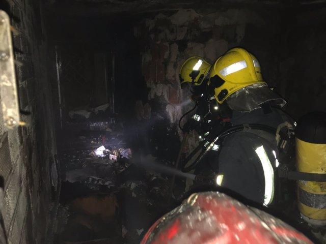 Bomberos de Málaga sofocando un incendio en una vivienda